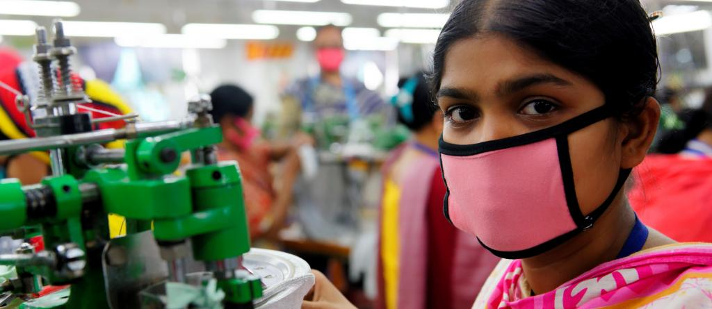 A Bangladeshi garment worker is seen wearing a face mask while producing clothing to be sold on major overseas markets. Photo: Marcel Crozet / ILO