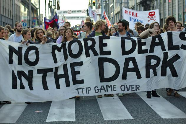 "Protest in Brussels against the TTIP and CETA free trade agreements. Protesters hold a banner that says ""No more deals in the dark. TTIP game over."" Photo: M0tty"