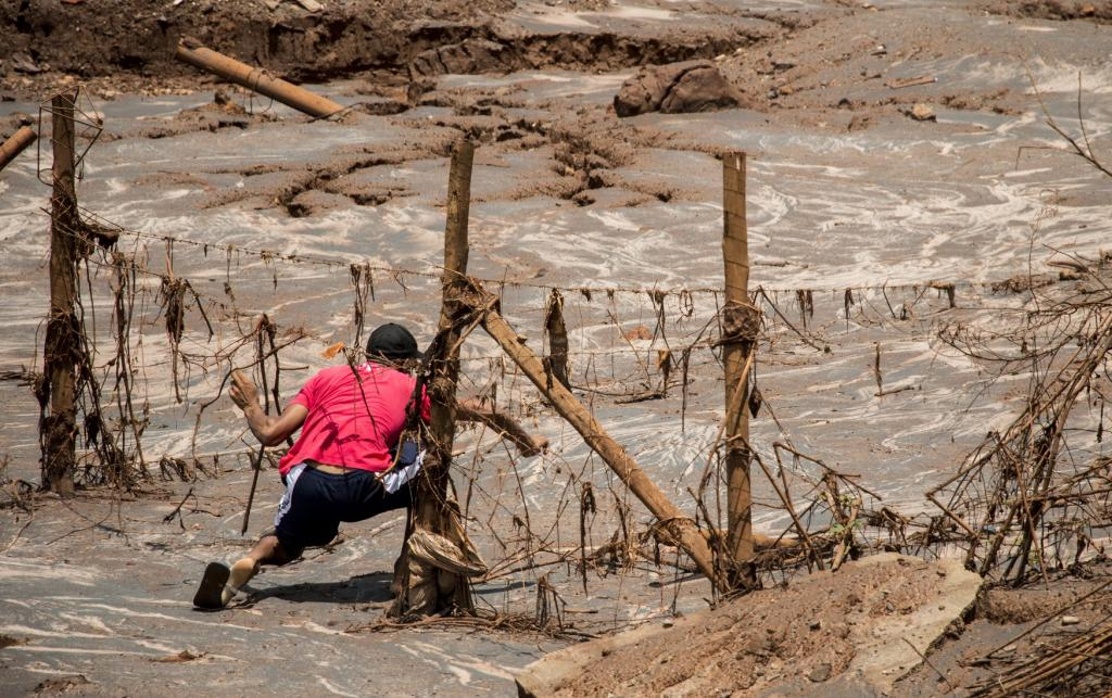 A man tries to reach his home a few weeks after the tidal wave of mud had dried up at the Samarco dam disaster