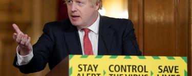 "Prime Minister Boris Johnson holds the Daily Covid-19 Digital Press Conference, gesturing and standing in front of a lectern with the government slogan on the front: ""Stay alert > Control the virus > Save lives"". Photo: Pippa Fowles / No 10 Downing Street."