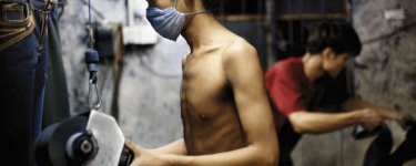 A worker sandblasts denim at a factory, topless but wearing a facemask. Photo: Justin Jin / Panos Pictures