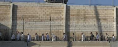 Palestinian workers in Israel protest dehumanising conditions at checkpoints. A queue of people stand in a line in front of a tall wall at a checkpoint. Source: Wikipedia