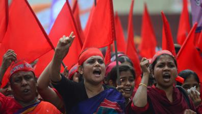 Women protest at a May Day Demonstration, with red headbands and flags. Dhaka, Bangladesh. Credit: MUNIR UZ ZAMAN / AFP / Getty Images
