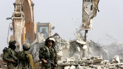 Israeli soldiers in front of bulldozers demolishing buildings. © EPA / Abed Al Hashlamoun