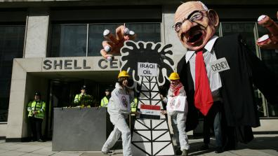 "Hands Off Iraqi Oil demo, 2008. Activists dressed as oil industry workers are outside of a Shell building, with a model of an oil drilling rig labelled ""Iraqi oil"", in front of a large caricature model labelled ""Chaney""."