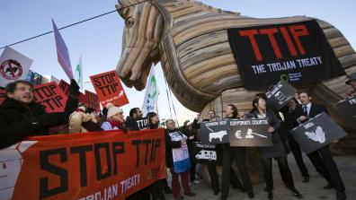 "A demonstration to 'Stop TTIP', with a giant inflatable wooden horse and a banner on it that reads ""TTIP: The Trojan Treaty""."