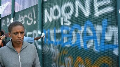 "A black person standing in front of the fence at at a protest at Yarl's Wood Immigration Removal Centre. Graffiti on the fence reads: ""No Borders! No one is illegal"". Photo: IDJ Photography"