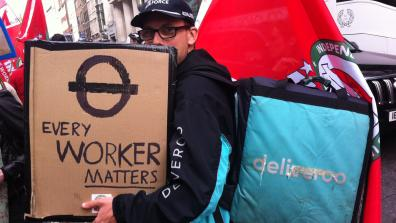A Deliveroo rider at a demonstration with an IWGB flag and a placard that reads 'Every worker matters'. Credit: Owen Espley