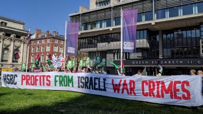 "Campaigners protest at HSBC's 2018 AGM, holding a giant banner reading ""HSBC profits from Israeli war crimes""."
