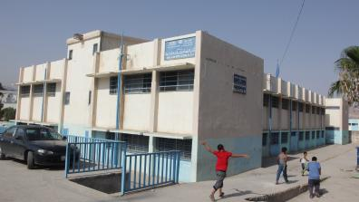 "A UNRWA school with children walking by outside. The sign on the front of the building reads: ""UNRWA North Amman Area, Department of Education, Baq'A Elem. Boys School no. 3&4. Photo: خليل مزرعاوي, / Addustour, Jordan Press & Publication Co. http://addustour.com/"