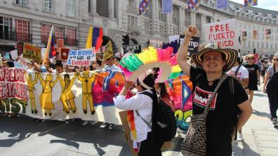 War on Want's Senior Programme's Officer Seb Munoz raises a fist at the front of a colourful Latin American contingent at a rally.